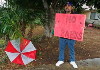 An irate dude protests outside Nadya Suleman's mother's house in Southern California.